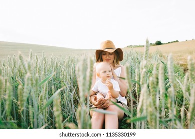 a young mother and her little child sitting near the wheat on a green background
