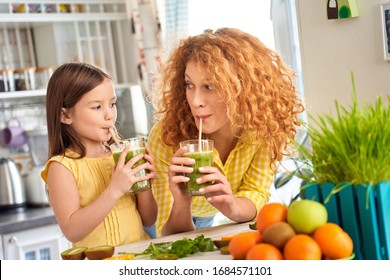 Young mother and her little child girl standing on kitchen together, enjoying healthy smoothie beverage, drink and enjoy fresh coctail