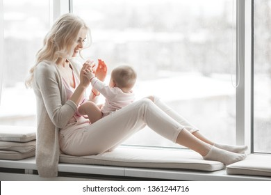 Young mother with her little cute baby daughter. Little baby girl and her mom. Mama with her child indoor.