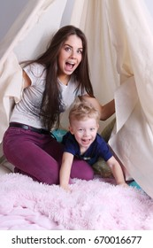 Young mother and her little cute son play in wigwam with pillows