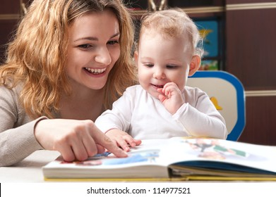 Young mother with her little daughter reading book