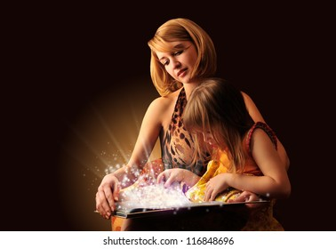 Young mother and her little daughter reading fairy book