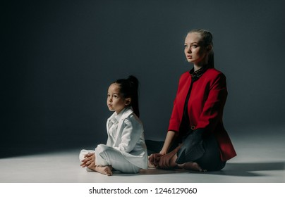 Young mother with her little daughter are sitting on floor in sukhasana pose of yoga.