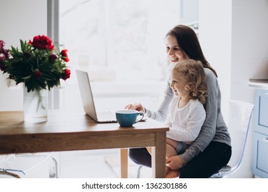 Young mother and her little daughter sitting on kitchen using a laptop