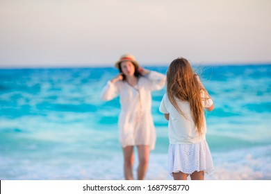 Young mother and her little daughter on the beach
