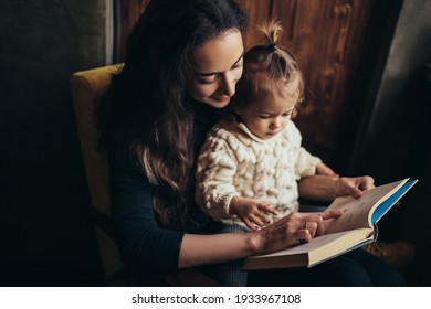 Young mother and her little daughter reading book together sitting in a comfortable chair.