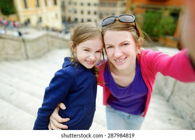 Young mother and her little daughter taking a photo of themself on Spanish steps in Rome