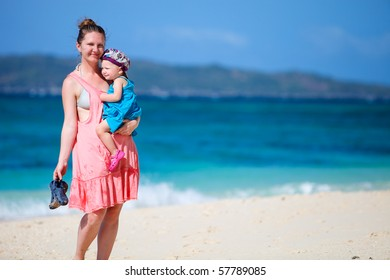 Young mother and her little daughter on tropical white sand beach