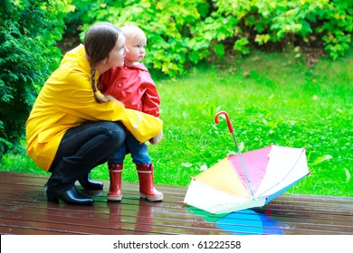 Young mother and her little daughter outdoors in colorful raincoats