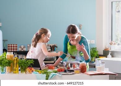 A young mother and her little daughter cooking bolognese sauce for spaghetti in the kitchen, there is steam escaping from the pan on cooking plate
