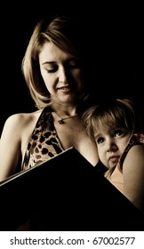 Young mother and her little daughter reading book before sleeping