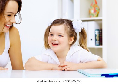 Young mother and her little girl studying together at home