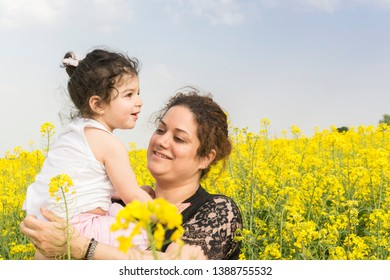 Young mother with her little girl at canola field, family enjoy together on canola farm
