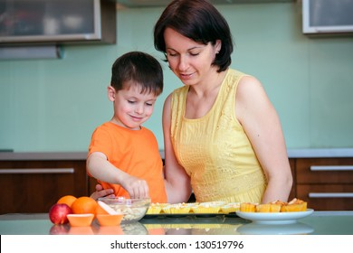 Young mother and her little son baking muffins