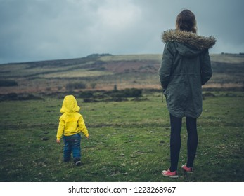 A young mother and her little toddler are standing on the moor