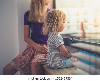 A young mother and her little toddler are looking out the window of a city apartment