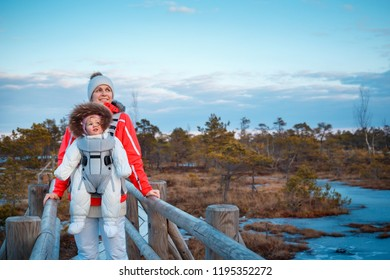 Young mother with her newborn daughter in a baby carrier outside walking on trail in swamp, Kemeri national park, Latvia