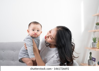 Young mother with her one years old little son dressed in pajamas are relaxing and playing in the living room at the weekend together, lazy morning, warm and cozy scene. Selective focus.