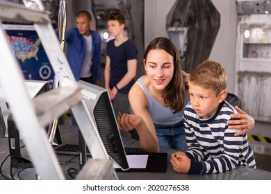 Young mother with her preteen son spending funny time in quest room decorated as lost underground shelter, trying to solve puzzle on computer monitor
