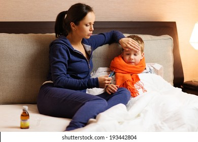 Young mother and her sick son in a bed