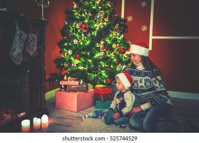 Young mother and her son by a fireplace on Christmas in home