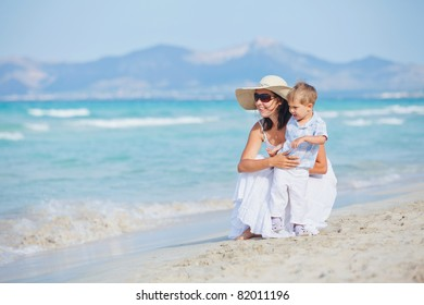 Young mother with her son on tropical beach vacation