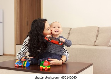 young mother and her son play and reading a book on sofa, lifestyle, real interior