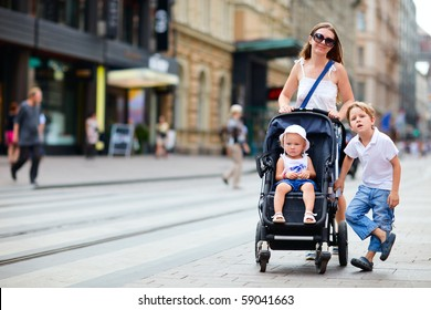Young mother with her son and toddler daughter in stroller walking in city center