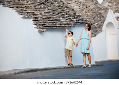 Young mother and her son walking narrow streets ot typical italian town, Alberobello, Italy
