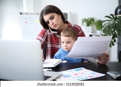 Young mother with her son working in office