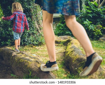 A young mother and her toddler are balancing on a log in the park