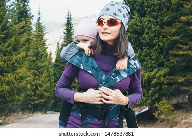 Young mother with her toddler daughter on back in ergonomic baby carrier outside in nature. Babywearing and active mother concept