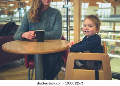 A young mother with her toddler is drinking coffee in a cafe