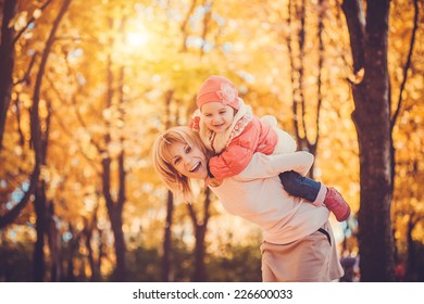 Young mother and her toddler girl have fun in autumn park