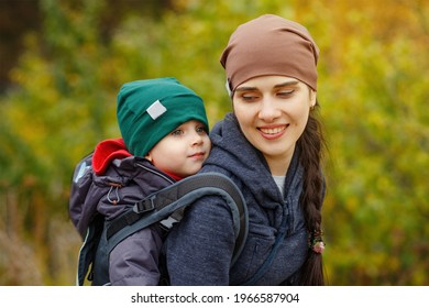 Young mother with her toddler kid boy on back in ergonomic baby carrier in autumn nature. Active mother concept.