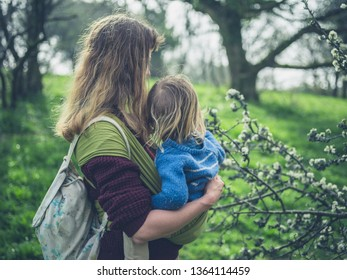 A young mother and her toddler are lookng at some lichen on a tree outdoors