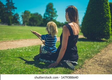A young mother and her toddler are relaxng in the park on a sunny summer day