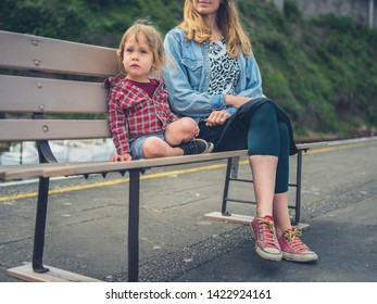A young mother and her toddler are sitting on a bench at the strain station