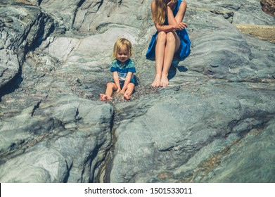 A young mother and her toddler are sitting on some rocks in the summer