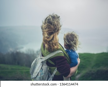 A young mother with her toddler in a sling is standing on top of a hill by the sea on a windy day