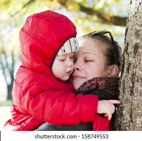 Young mother and her toddler son in autumn park