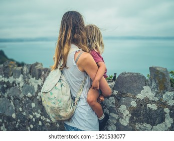 A young mother and her toddler are standing by a wall on the coast