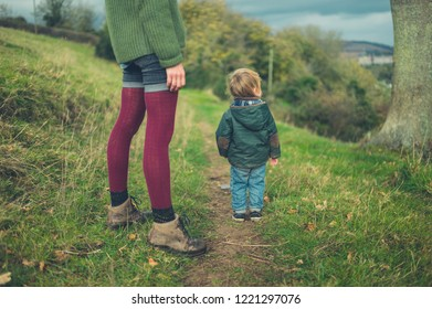 A young mother and her toddler are walking in the countryside