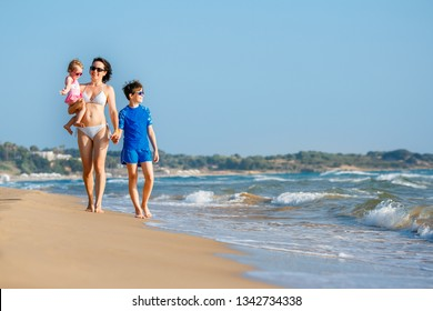 Young mother with her two kids on tropical beach during summer holiday vacation