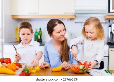 Young mother and her two kids making vegetable salad