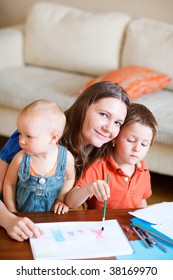 Young mother and her two kids drawing together. Can be used also in kindergarten/daycare context.