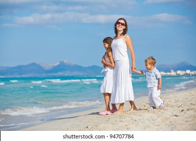 Young mother with her two kids on tropical beach vacation