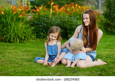 Young mother and her two little daughters at summer