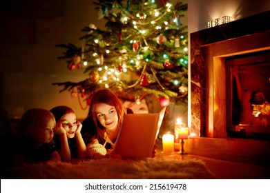 Young mother and her two little daughters reading a book by a Christmas tree in cozy living room in winter