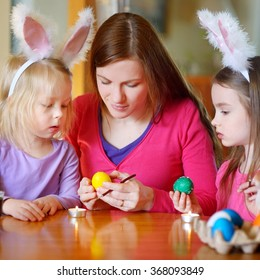 Young mother and her two little daughters painting colorful Easter eggs at home